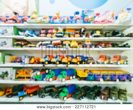Blurred Of Kids Toy Store Background With Bokhe. Shelves With Toy Cars In Kids Toy Shop Interior, Co
