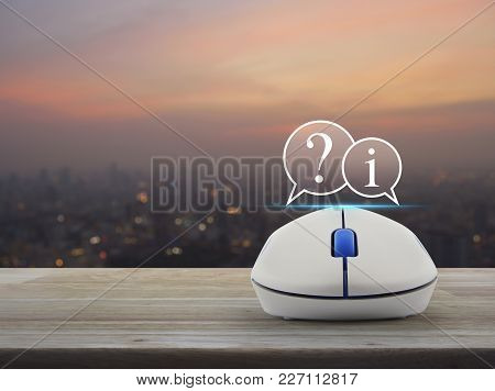 Question Mark And Information Chat Icon With Wireless Computer Mouse On Wooden Table Over Blur Of Ci