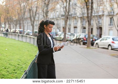 Online Store Consultant Speaking With Customers By Smartphone During Walk Outdoors. Young  Woman Dre