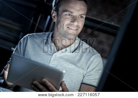 Tech Lifestyle. Happy Male Entrepreneur Sitting At A Table And Holding A Tablet Computer While Focus