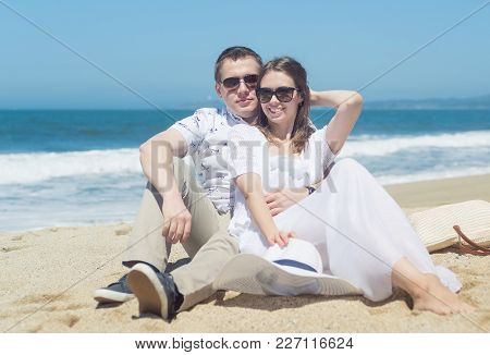 Young Romantic Couple In Sunglasses And White Outfit Spending Vacation Or Weekend On The Beach, Wear