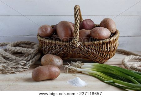 Wicker Basket With Fresh Potato Tubers Green Onions And Salt On The Table