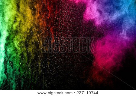 Explosion Of Color Powder On Black Background. Splash Of Color Powder Dust On Dark Background.