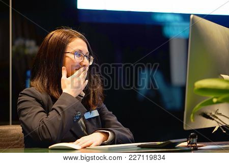 Hotel Manager. A Brunette Woman-reception Shocked Sitting In Front Of The Monitor Of Computer. Funny