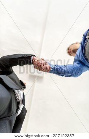 Two Businessmen Shaking Hands On A Deal Viewed From Directly Below Looking Up, One In A Suit And One
