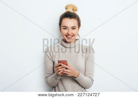 Happy Cheerful Woman With Hair Bun Nude Makeup Wearing In Sweater Standing Indoors With Her Smartpho
