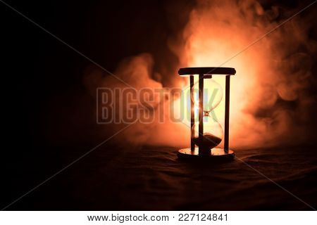 Time Concept. Silhouette Of Hourglass Clock And Smoke On Dark Background With Hot Yellow Orange Red