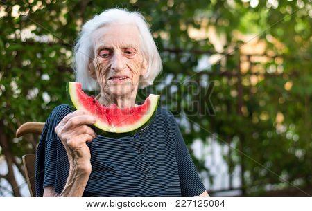 Senior Woman Eating Watermelon Fruit In The Backyard