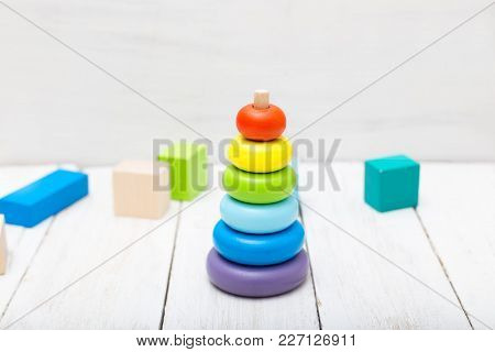 Ecological Wooden Toys On White Wooden Background. Multicolored Wooden Pyramid
