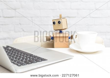 A Robot With Hands Sitting At The Table And Working Behind A Laptop. Artificial Intelligence