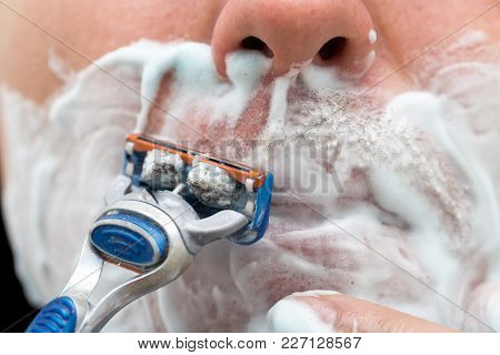 The Man Is Shaving With Foam Machine .