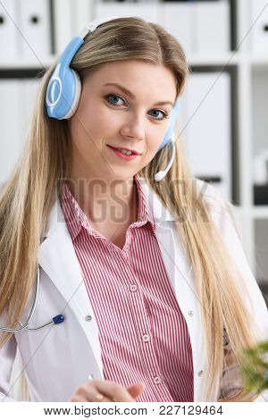 A Beautiful Feminine Blonde Doctor Talking To Patient Over Wireless Headset Advises A Medical Proble