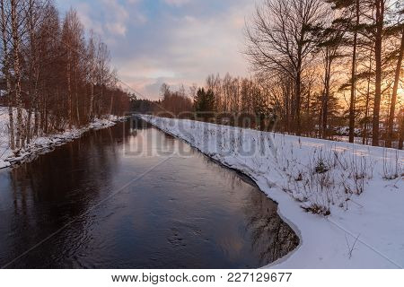 Straight Channel And A Beautiful Sunset Sky With Snow On The Side