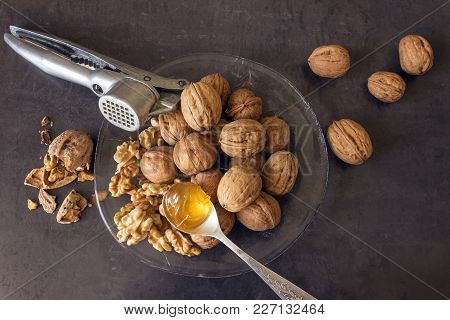 Walnuts Lie In A Glass Dish Along With A Nutcracker. Spoon With Golden Honey Lies On The Cleaned Nut