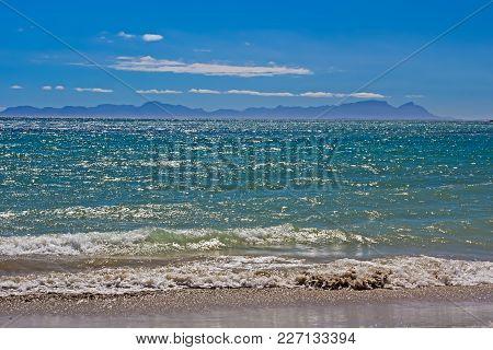 View Across Blue-green Choppy Waters In False Bay Towards Table Mountain