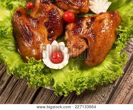 Baked Chicken Wings With Frsh Vegetables Over Old Wooden Background