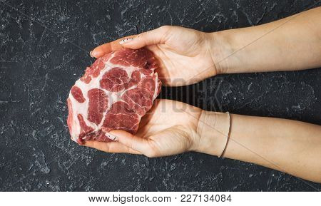 Raw Pork Meat. Woman Hands Holding One Slice Of Steak.