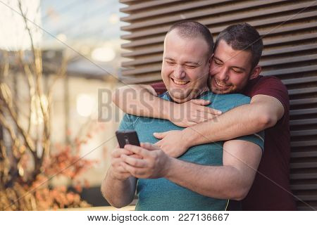 Cute Gay Couple Chatting About Online Content On Their Phone