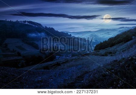 Rural Valley With Forested Hills At Night In Full Moon Light. Beautiful Summer Landscape In Carpathi
