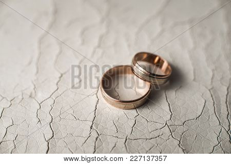 Pair Of Wedding Golden Rings On The White Cracked Skin. Selective Focus