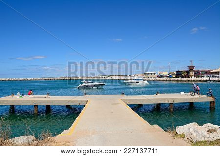 Vilamoura, Portugal - June 6, 2017 - Locals On A Concrete Jetty At The Harbour Entrance With A Boats