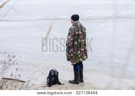 Young Man Walking On Beach Watching The Frozen Water In A Military Rain Coat, Winter Fishing Or Hunt