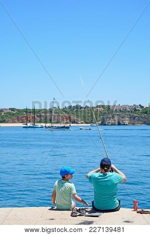 Portimao, Portugal - June 7, 2017 - Man And Boy Fishing From The Breakwater With Views Towards The B