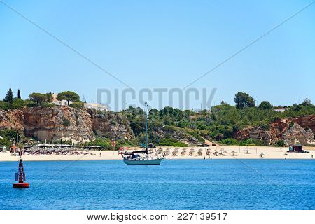 Portimao, Portugal - June 7, 2017 - Yacht Moored In The Sea With The Beach To The Rear And People En