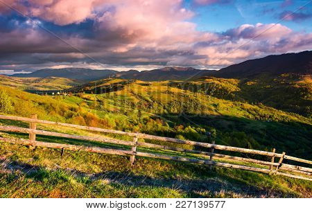 Gorgeous Evening In Mountainous Rural Area. Fence Along The Grassy Slope. Mountain Ridge Under The P