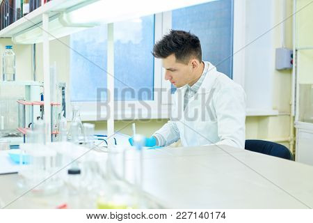 Profile View Of Handsome Young Researcher Wearing Rubber Gloves And White Coat Sitting At Desk And T