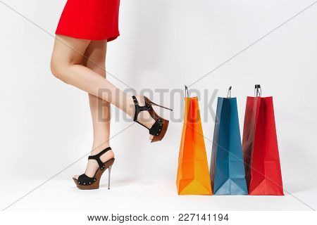 Slender Long Female Legs In Black Sandals, Caucasian Woman In Red Dress Standing Near Multi Colored