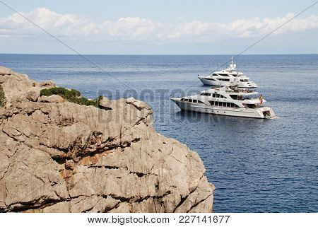 MAJORCA, SPAIN - SEPTEMBER 6, 2017: Super yachts moored off the Torrent de Pareis gorge at Sa Calobra on the Spanish island of Majorca. The gorge is one of the top tourist attractions on the island.