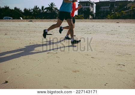 Healthy Lifestyle Concept. Two Runners Run Along The Beach In The Morning
