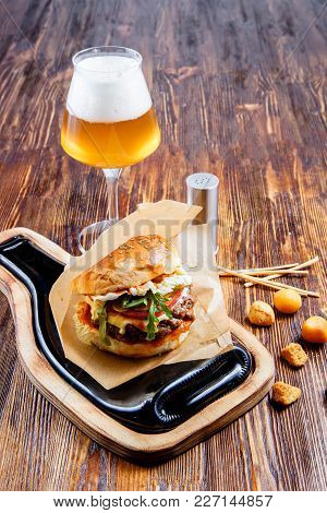 Tasty Hamburger With A Glass Of Beer On Wooden Counter.