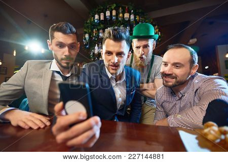 Group Of Friends Gathered Together In Modern Pub And Watching Funny Video On Smartphone While Celebr