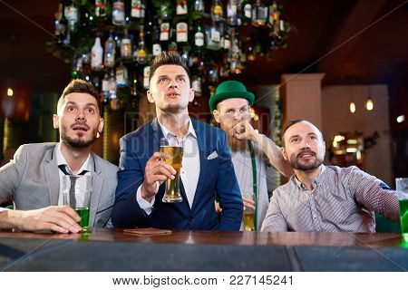 Bearded Men Sitting At Bar Counter And Watching Rugby Match With Concentration, Red-haired Man Weari