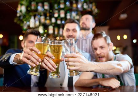 Group Of Cheerful Friends Clinking Beer Glasses Together While Sitting At Bar Counter And  Celebrati