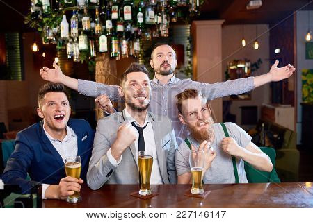 Joyful Group Of Friends Celebrating Victory Of Their Favorite Football Team While Sitting In Modern