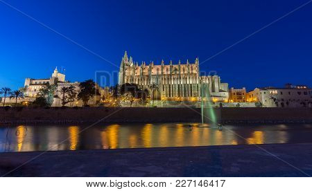 Palma De Mallorca Cathedral Sunset. Night Lighting Reflected In Water. Balearic Islands Of Spain