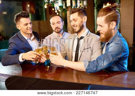 Celebrating Completion Of Hard Working Day: Group Of Cheerful Colleagues Clinking Beer Glasses Toget