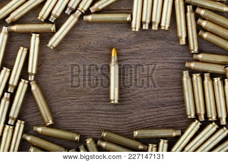 M-16 Bullet On Wooden Table Close-up. High Resolution Photo.