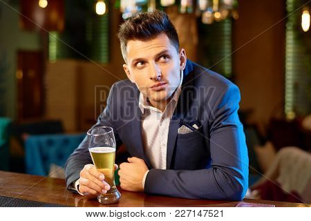 Handsome Young Entrepreneur Wearing Stylish Suit Watching Soccer Match And Drinking Ale While Spendi