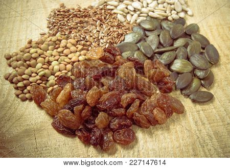 Flaxseed, Pumpkin, Raisins, Lentils And Sunflower Seeds In Wooden Spoons. Seeds - A Concept Of Healt