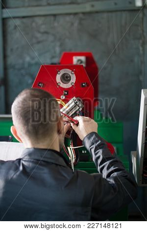 Electrician Works With Energy Panel And Machinery Equipment On Plant, Rear View