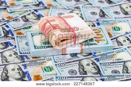 Folded Five Thousandths Banknotes Of Russian Roubles Over Heap Of One Hundred American Dollar Bills