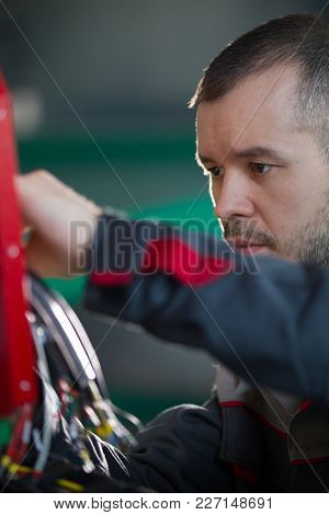 Electrician Builder Engineer Screwing And Testing Equipment In Fuse Box, Portrait