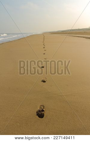 Trail Of Footsteps In The Sand Of A Deserted Beach