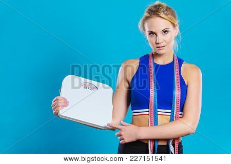 Healthy Lifestyle. Fitness Woman With Many Measure Tapes Holding Weight Scale Studio Shot Blue Backg