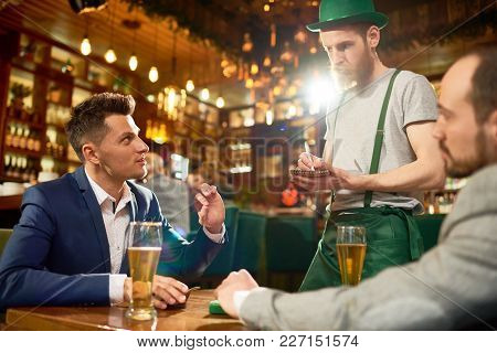 Celebrating St. Patricks Day In Cafe: Two Friends Wearing Suits Sitting At Table And Making Order Wh