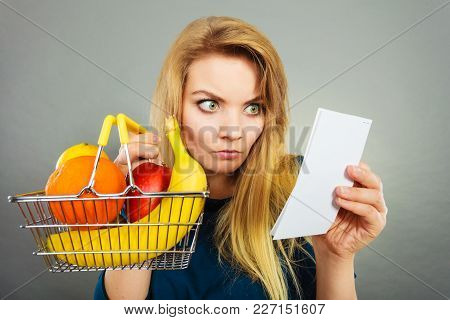 Shocked Woman Holding Shopping Basket With Fruits Looking At Bill Receipt Being Scared Of Huge Price